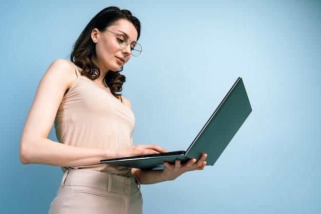 Vista dal basso. ritratto di una bella donna d'affari che lavora al computer portatile
