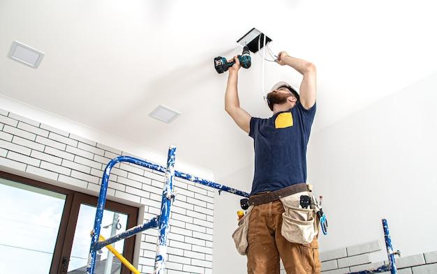 Vista dal basso professionale in tuta con strumenti sul sito di riparazione. concetto di ristrutturazione della casa.