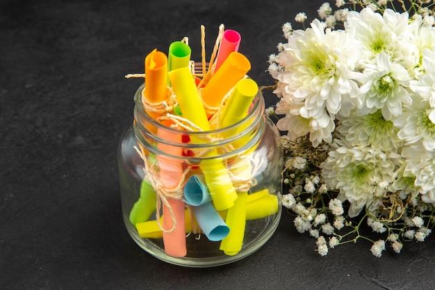 Vista dal basso scorrere le carte dei desideri colorate in fiori di vaso su sfondo scuro