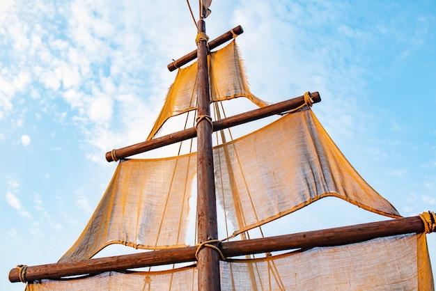 Vista dal basso di un albero di nave con vele beige oscilla contro un cielo blu con nuvole di sole calde giornate estive soleggiate. concetto marino e di avventura