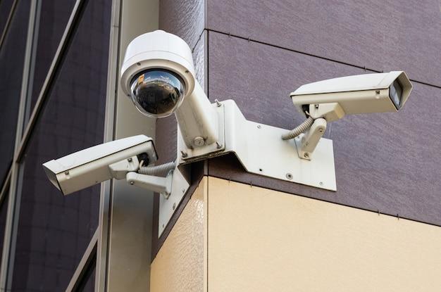 Una vista dal basso di tre telecamere di sorveglianza bianche sull'edificio per uffici con giallo pallido