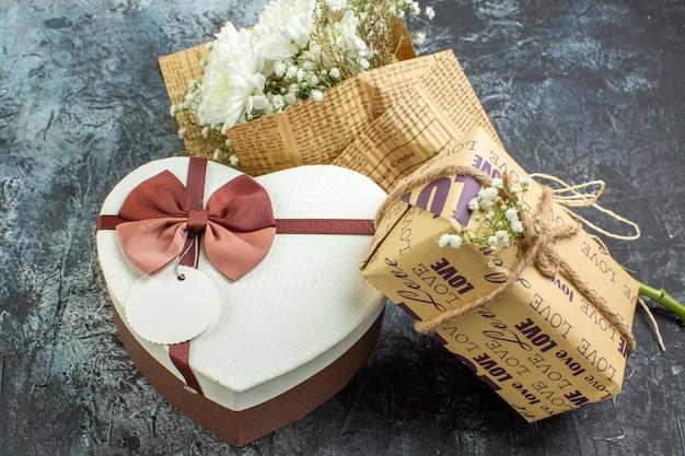 Vista dal basso dettagli di san valentino bouquet di fiori scatola regalo a forma di cuore su sfondo scuro