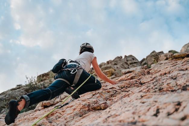 Vista dal basso di una donna con i capelli castani che scala una montagna