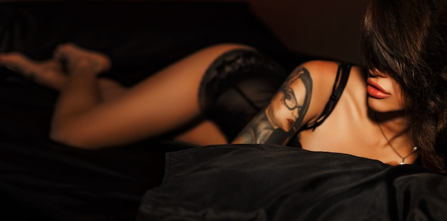 Foto del boudoir della ragazza sexy che indossa biancheria intima alla moda che posa nella camera da letto.
