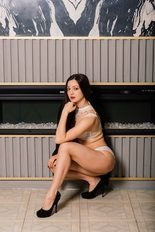 Sessione di boudoir con una giovane donna caucasica bruna con lingerie bianca e nera