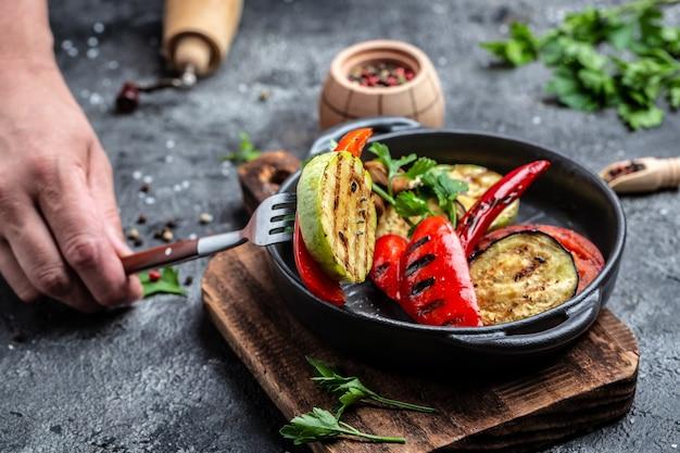 Abbondanza di verdure grigliate colorate servite su una padella in ghisa. assortimento vari barbecue cibo vegano