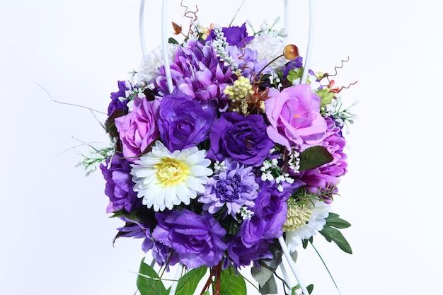 Mazzo del fiore porpora artificiale fondo variopinto e bianco
