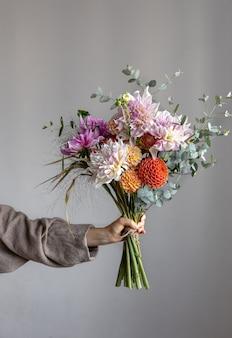 Un mazzo di bellissimi crisantemi nello spazio della copia della mano di una donna