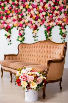 Bouquet di bellissimi fiori in scatola e divano vintage su sfondo colorato di fiori estivi