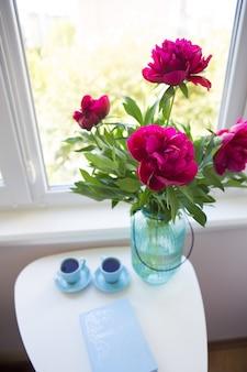 Un bouquet di bellissime peonie e due tazze