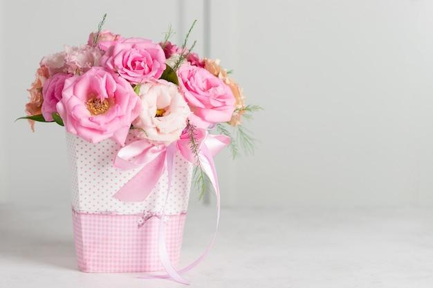 Mazzo di belle rose rosa e eustomas in una scatola