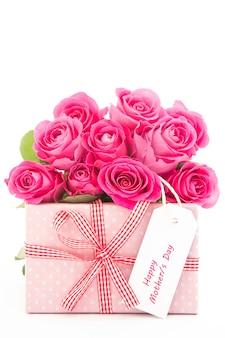 Mazzo di belle rose rosa accanto ad un regalo rosa con una carta felice di giorno di madri su backgroun bianco