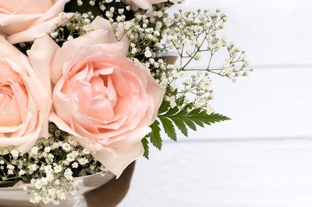 Un mazzo di belle rose rosa su fondo di legno bianco.