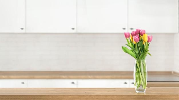 Mazzo di bei tulipani sul piano del tavolo da cucina sul fondo della cucina della sfuocatura con il posto per l'esposizione del prodotto del montaggio