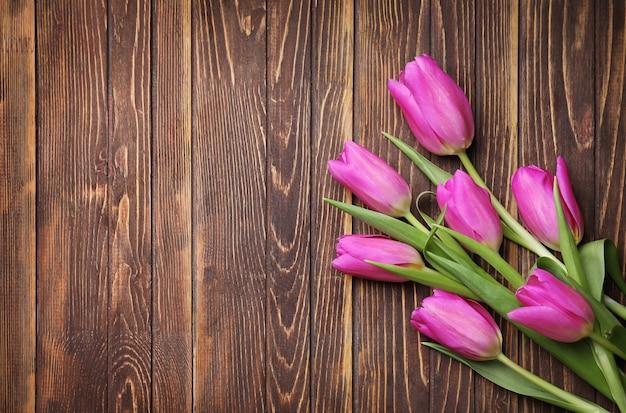 Mazzo di bei tulipani su superficie di legno