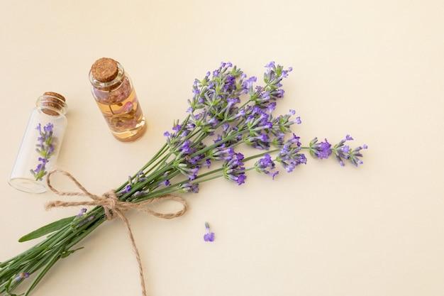 Bouquet di lavanda in fiore e piccole bottiglie di vetro con olio essenziale di lavanda e fiori
