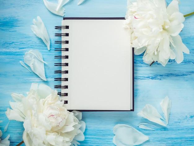Bouquet di fioriture, peonie bianche e una pagina vuota del blocco note