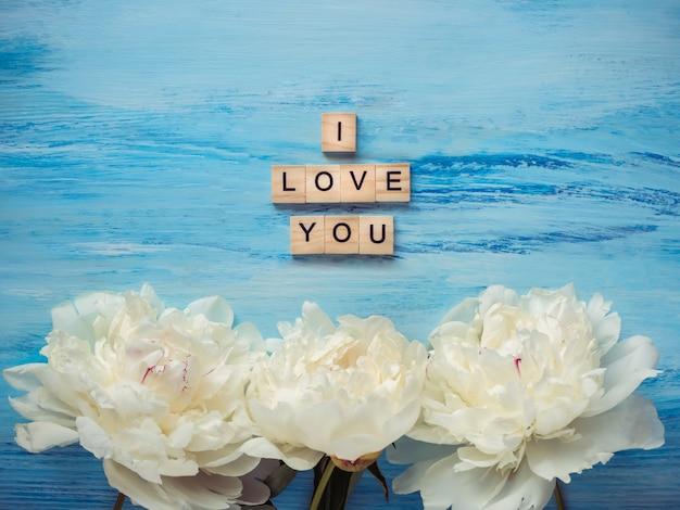 Bouquet di fioriture, peonie bianche e la parola amore