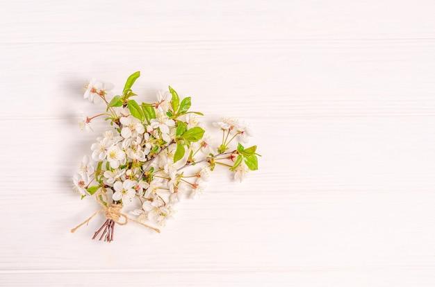 Un bouquet di ciliegio in fiore su una superficie bianca