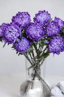 Un bouquet di crisantemi blu in un vaso di vetro su sfondo bianco.