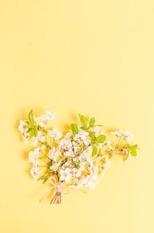 Un bouquet di rami di ciliegio in fiore su una superficie gialla