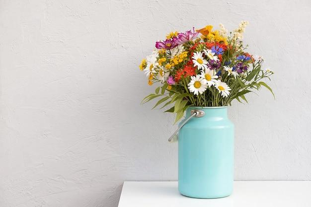 Bouquet di fiori luminosi in vaso di latta sul muro di pietra grigia di sfondo. modello per cartolina. concetto festa della donna, festa della mamma, ciao estate o ciao primavera.