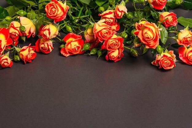 Bouquet di rose arancio brillante su sfondo di pietra nera.