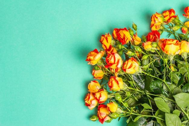 Bouquet di rose arancio brillante su sfondo turchese