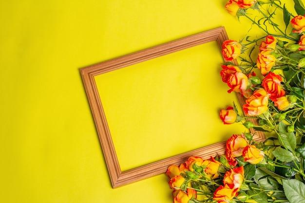 Bouquet di rose arancio brillante con cornice in legno su sfondo giallo brillante