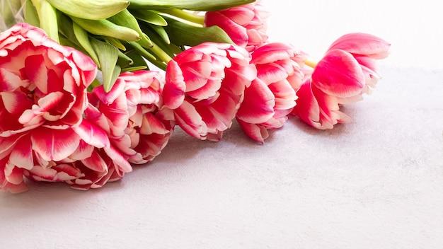 Un bouquet di tulipani rosa e rossi luminosi giace su un tavolo di pietra grigia con posto per il testo. focalizzazione morbida.
