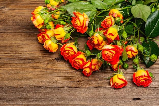 Mazzo delle rose gialle luminose sulla vecchia tavola di legno