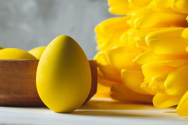 Bouquet di tulipani gialli luminosi e uovo di pasqua, in piedi sulla superficie di legno bianca sulla superficie grigia