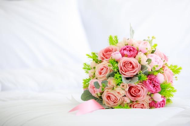Un mazzo di fiori colorati in tessuto finto su copriletto bianco con copia spazio.