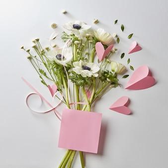 Bouquet e biglietto per il tuo testo, cuori rosa fatti di carta su sfondo bianco