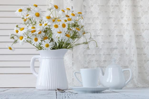 Mazzo di camomilla in un vaso sulle vecchie schede.