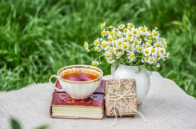 Bouquet di camomille, confezione regalo e una tazza di tè Foto Premium