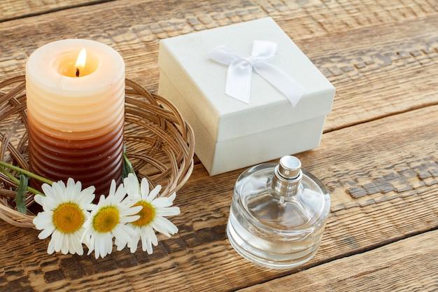 Bouquet di camomille, profumo, candela accesa e regalo bianco o scatola regalo su tavole di legno. vista dall'alto. concetto di vacanza.