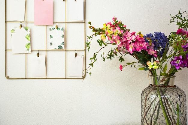 Bouquet di fiori colorati parete bianca e cartoline appese, interni moderni retrò