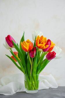 Bouquet di tulipani naturali colorati in un vaso di vetro con acqua su uno sfondo di cemento.