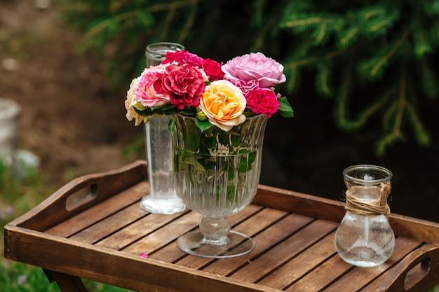 Bouquet di rose colorate in un vaso di vetro su una gamba su un vassoio di legno