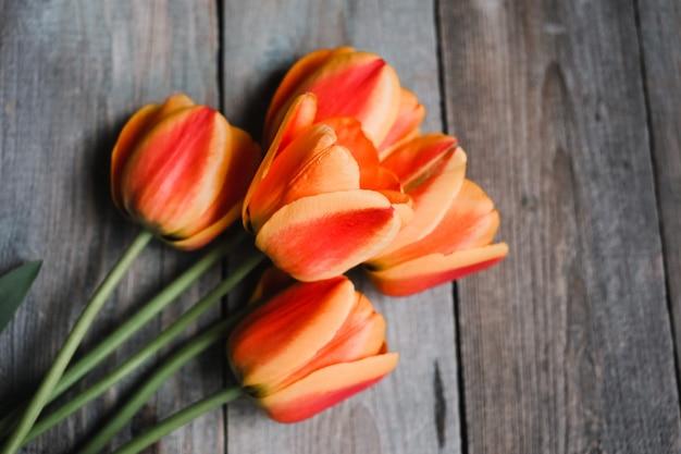 Bouquet di tulipani colorati sul vecchio tavolo in legno. vista dall'alto