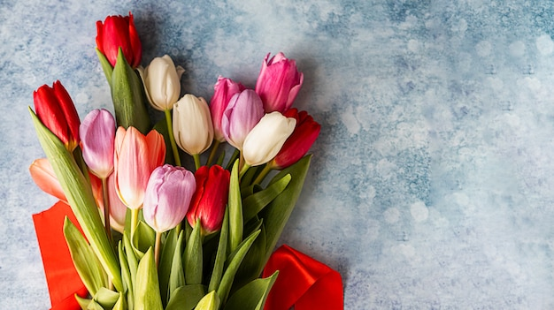Bouquet di tulipani colorati con nastro rosso