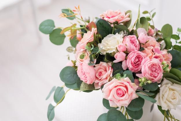 Composizione del mazzo con le belle rose in un contenitore di regalo.