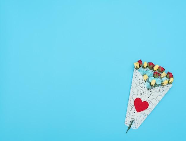 Bouquet di fiori artigianali avvolti in un fascio di pizzo bianco su sfondo blu.