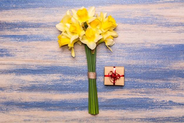 Un bouquet di narcisi, un regalo con un nastro rosso su uno sfondo di legno. fiori gialli di primavera. vernice peeling blu. design piatto laici, vista dall'alto.
