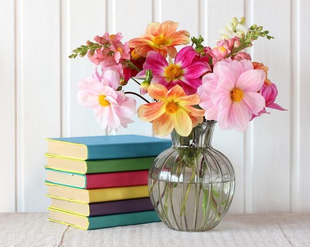 Bouquet di dalie e libri di testo in copertina a colori.