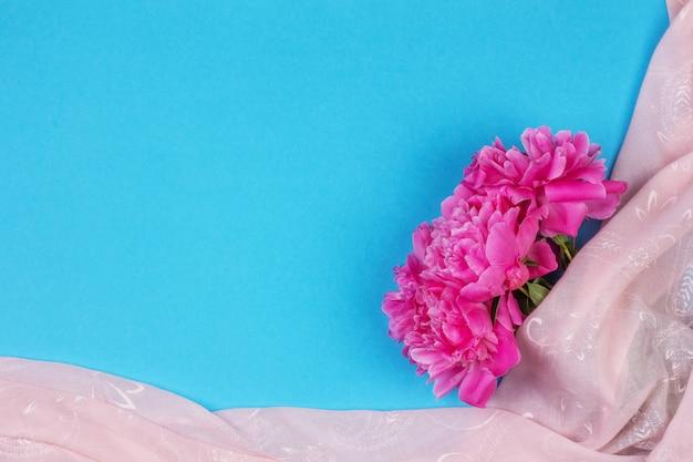 Bouquet di fiori di peonia rosa scuro da vicino e tessuto rosa su sfondo blu con spazio di copia