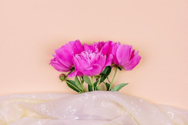 Bouquet di fiori di peonia rosa scuro da vicino e tessuto rosa su sfondo color sabbia