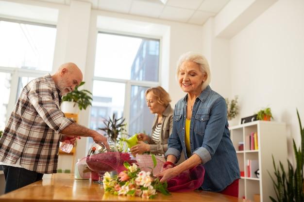 Disegno del mazzo. bella donna dai capelli grigi in piedi vicino ai fiori mentre crea il design del bouquet