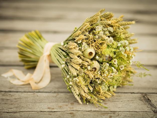 Bouquet di fiori secchi. natura morta con spighe di grano e fiori di campo gialli e bianchi su fondo in legno